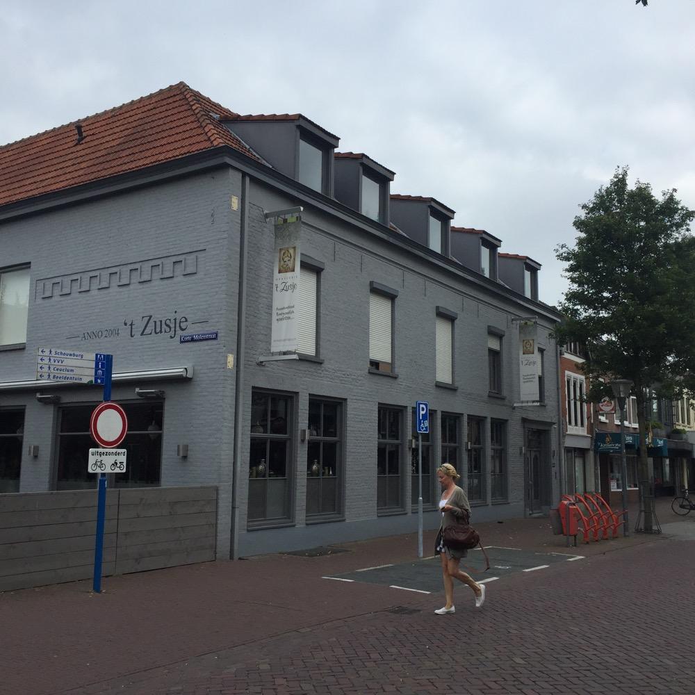 vrouw loopt op baksteen week voor grijs gebouw met 't Zusje
